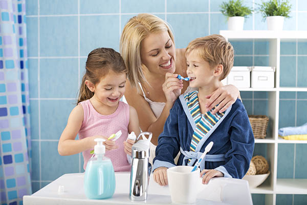 Smiling Family Brushing their teeth together
