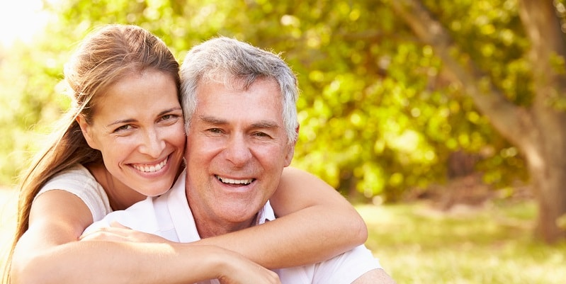 I happy smiling couple with perfect teeth thanks to affordable All-on-4® dental implants.