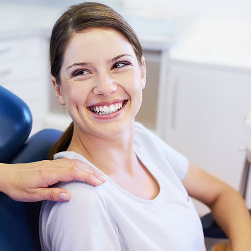 A dental hygienist comforting a patient in the dental chair