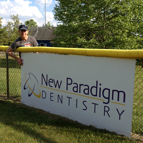 Dr. Jim Burden standing next to a local banner for New Paradigm Dentistry
