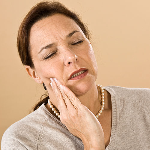 A middle-aged woman holding her jaw in pain