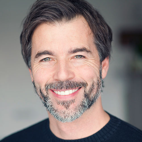 A middle age man with a beard smiling