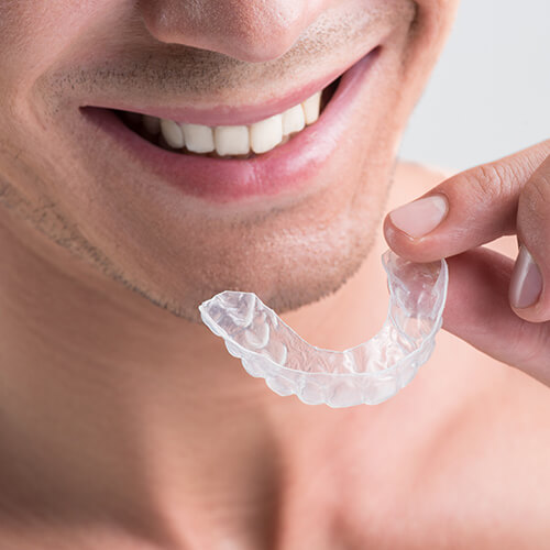 Close up of a man holding Invisalign clear aligners